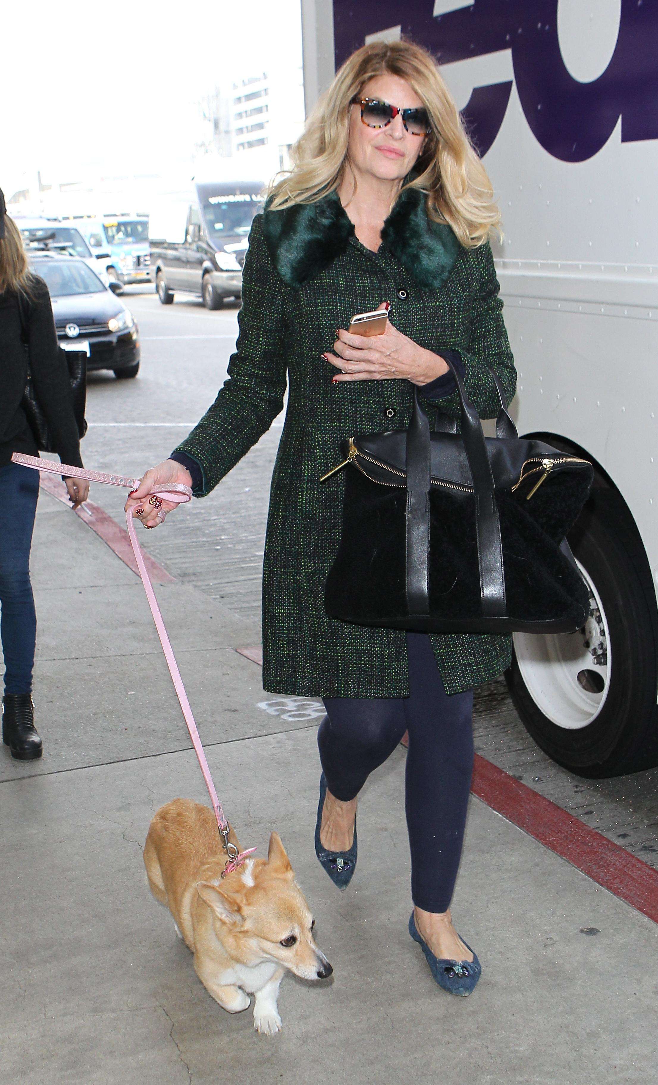 Kirstie Alley arrives for a flight with her dog by her side