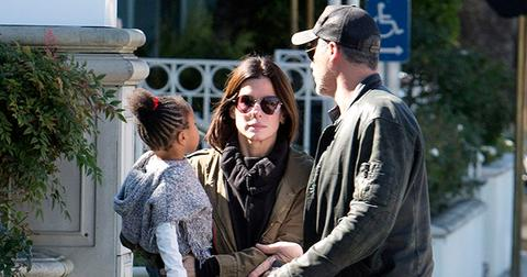 EXCLUSIVE: *** Premium Exclusive Rates Apply*** Sandra Bullock doesn't look to impressed with boyfriend Bryan Randall as she holds her daughter Laila while they pick up coffee in Studio City, CA
