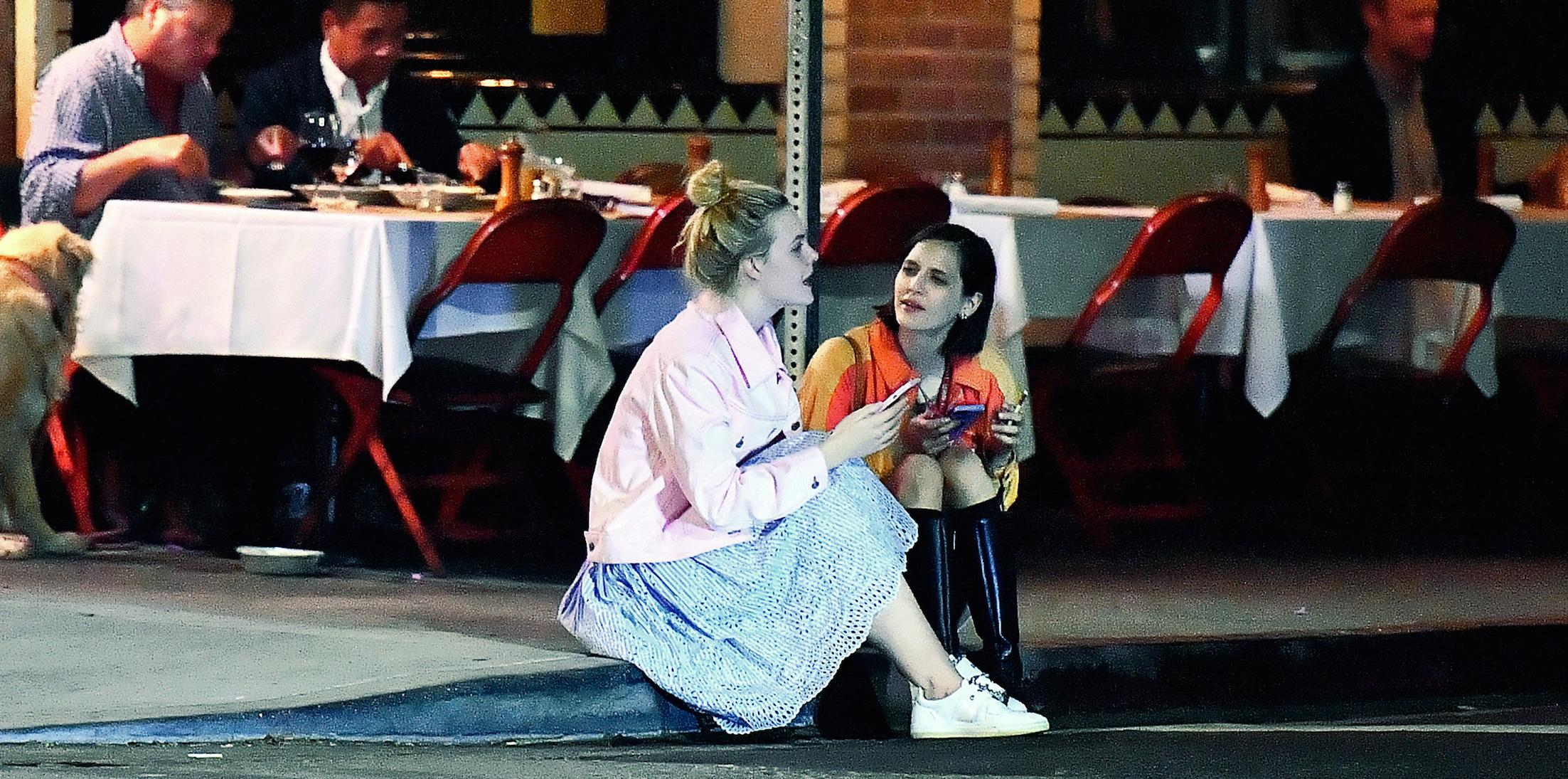 EXCLUSIVE: Elle Fanning sits on a curb and chats with a friend after dinner at Little Dom's in Los Feliz, CA.