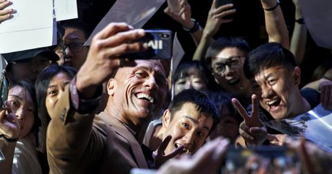 The Rock takes a selfie with adoring fans on the red carpet.