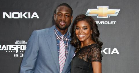 Dwayne Wade, in a blue jacket, white pants, and red shoes, poses with Gabrielle Union who wears a black dress and black wedges.