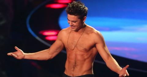 A shirtless Zac Efron stands on a stage with his arms widespread.