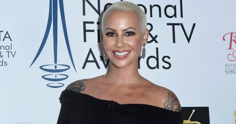 Amber Rose wears an off-the-shoulder black top and smiles on the red carpet.