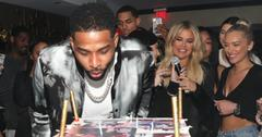 Tristan Thompson blows out candles on his birthday cake as Khloe Kardashian and others look on. Tristan is currently famous for being one of the most talked about cheating celebrities of 2018
