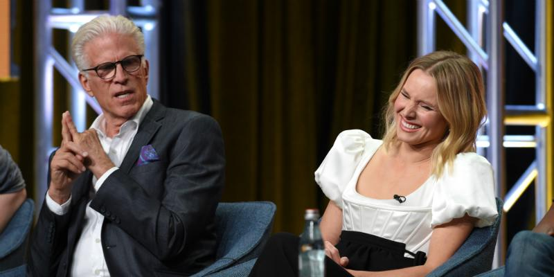 Kristin Bell sits on stage, laughing, as Ted Danson sits next to her watching.
