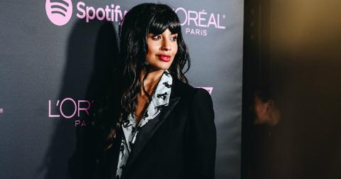 Jameela Jamil poses on the red carpet in a black jacket and patterned shirt.