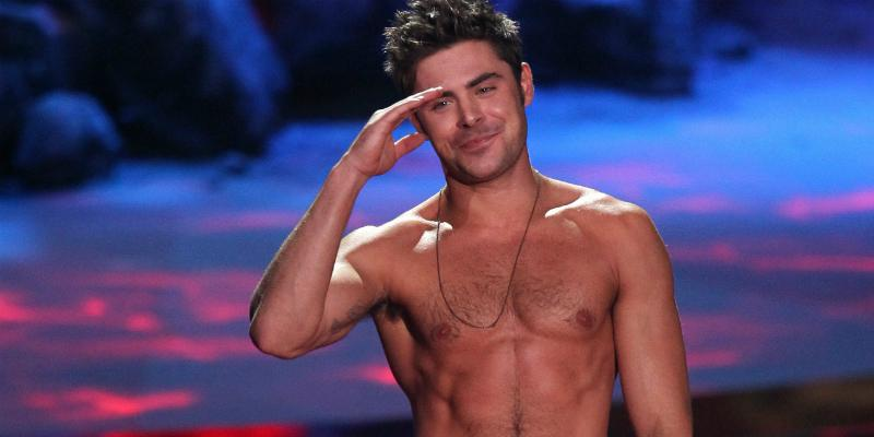 Zac Efron stood on the MTV Movie Awards stage, shirtless, with black dress slacks, looking all kinds of hot.
