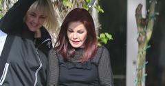 Priscilla Presley is greeted by a mystery man when she arrives at The Wise School in Los Angeles. Priscilla left an hour after arriving carrying a pamphlet with a photo of Elvis Presley, her former husband, on it.