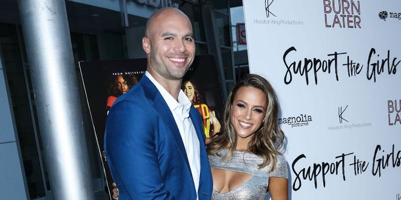 Mike Caussin waering Blue suit and White Shirt With Wife Jana Kramer Wearing Silver cut out Gown