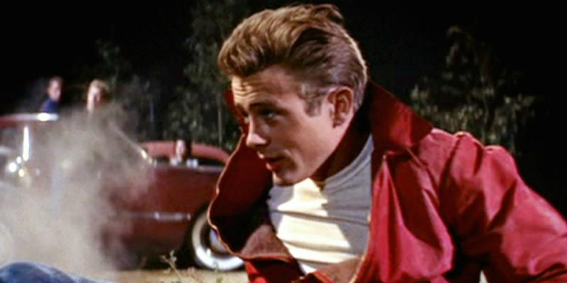 James Dean smoldered in his classic red jacket and white T-shirt in a scene from his triumphant film, Rebel Without a Cause.